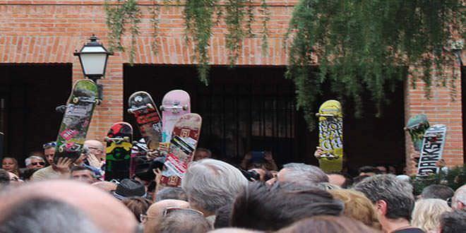 Asistentes a la concentración en memoria de Ignacio Echeverría alzan sus monopatines al cielo.