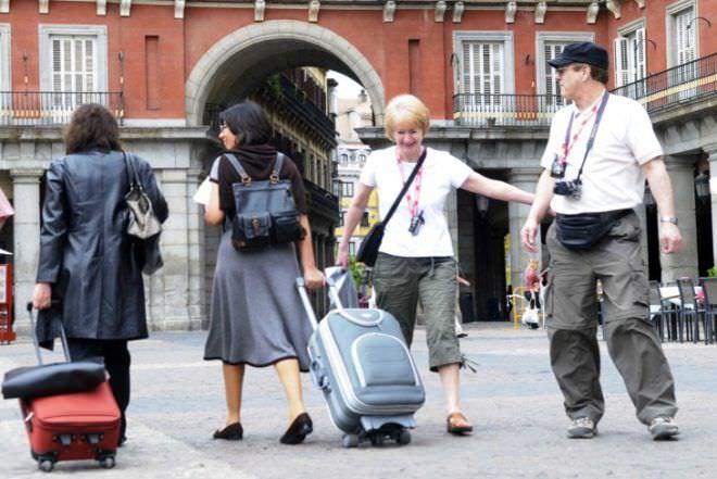 Turistas pasean por Madrid en busca de su alojamiento.